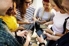 Amigos adultos jovenes que usan concepto de la cultura joven de los smartphones junto al aire libre Imágenes de archivo libres de regalías