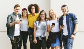 Amigos adultos jovenes que usan el Cu de la juventud de los smartphones junto al aire libre Fotografía de archivo libre de regalías
