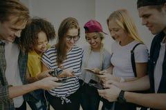 Amigos adultos jovenes que usan el Cu de la juventud de los smartphones junto al aire libre Foto de archivo