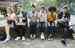 Amigos adultos jovenes que usan el Cu de la juventud de los smartphones junto al aire libre Fotografía de archivo