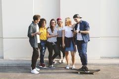 Amigos adultos jovenes que usan el Cu de la juventud de los smartphones junto al aire libre Imagen de archivo