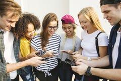 Amigos adultos jovenes que usan el Cu de la juventud de los smartphones junto al aire libre Imágenes de archivo libres de regalías