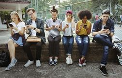 Amigos adultos jovenes que usan el Cu de la juventud de los smartphones junto al aire libre Foto de archivo libre de regalías