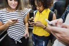 Amigos adultos jovenes que usan smartphones en el subterráneo Imágenes de archivo libres de regalías