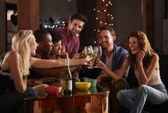 Amigos adultos novos que têm um partido em casa que faz um brinde foto de stock