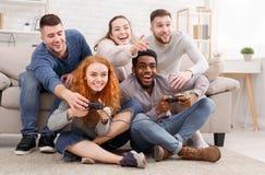 Amigos adultos que juegan a los videojuegos, sentándose en piso en casa fotografía de archivo