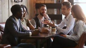 Amigos africanos e caucasianos que fazem o aperto de mão apostado na reunião do café filme