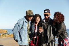 Amigos africanos sonrientes que caminan al aire libre usando el teléfono móvil fotografía de archivo