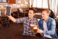 Amigos agradables que beben la cerveza Fotografía de archivo libre de regalías