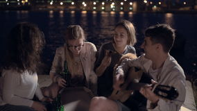Amigos alegres em um partido que come a pizza, a cerveja bebendo e jogando a guitarra filme