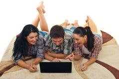 Amigos alegres en la alfombra usando la computadora portátil Imagen de archivo