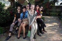 Amigos alegres en roca en parque Imagen de archivo libre de regalías