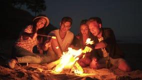Amigos alegres jovenes que se sientan por el fuego en la playa por la tarde, cocinando la melcocha en los palillos junto tirado a almacen de metraje de vídeo