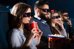 Amigos alegres junto en el teatro de película Foto de archivo libre de regalías