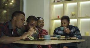 Amigos alegres negros que disfrutan del encuentro en café almacen de video