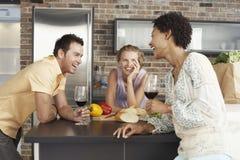 Amigos alegres no contador de cozinha Imagens de Stock