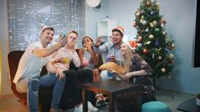 Amigos alegres nos chapéus de Santa que fazem a chamada video pelo smartphone na festa de Natal filme
