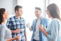 Amigos alegres que bebem o café Imagem de Stock