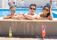 Amigos alegres que beben los cócteles en la piscina Imagen de archivo libre de regalías