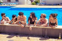 Amigos alegres que beben los cócteles en la piscina Imágenes de archivo libres de regalías