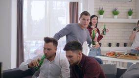 Amigos alegres que brindam garrafas de cerveja e que jogam os jogos de vídeo que sentam-se no sofá no backgrounf da empresa das a vídeos de arquivo
