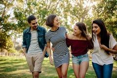 Amigos alegres que caminan en el parque fotografía de archivo libre de regalías