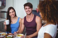 Amigos alegres que comem o café da manhã foto de stock