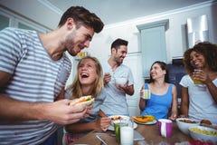 Amigos alegres que comem o café da manhã na tabela fotografia de stock