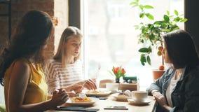 Amigos alegres que comem a sobremesa saboroso do alimento no café e que falam rindo da tabela vídeos de arquivo