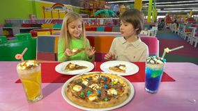 Amigos alegres que comen la pizza del chocolate durante cena en el café de los niños almacen de video