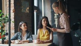 Amigos alegres que conversam no café que fala então à empregada de mesa no avental que faz a ordem filme