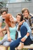 Amigos alegres que cuelgan hacia fuera por el campus de la universidad fotografía de archivo