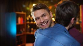 Amigos alegres que encontram-se no sorriso da barra, fazendo o gesto do cumprimento, prazer filme