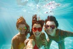 Amigos alegres que hacen el selfie subacuático en piscina Foto de archivo