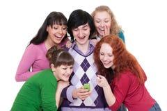 Amigos alegres que miran el teléfono celular Imágenes de archivo libres de regalías
