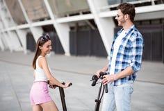 Amigos alegres que montam o 'trotinette' do pontapé Fotografia de Stock Royalty Free