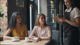 Amigos alegres que pedem o alimento no café que fala ao sorriso fêmea amigável da empregada de mesa video estoque