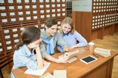 Amigos alegres que se preparan para el examen imagen de archivo
