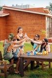 Amigos alegres que se sientan en la cerveza de consumición de la tabla y que se divierten Foto de archivo