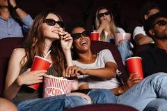 Amigos alegres que se sientan en película del reloj del cine Imagen de archivo