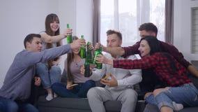 Amigos alegres que sentam-se no sofá na frente da tevê que come a pizza e que faz o brinde com partido das garrafas de cerveja em filme