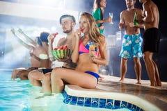 Amigos alegres que sonríen, disfrutando, descansando en el partido cerca de piscina foto de archivo libre de regalías