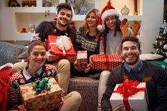 Amigos alegres que sostienen las cajas con los regalos de la Navidad Fotografía de archivo libre de regalías