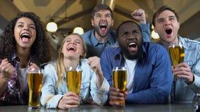 Amigos alegres que tintinean los vidrios de cerveza, celebrando la victoria del equipo en barra, ocio almacen de metraje de vídeo