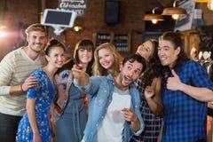 Amigos alegres que toman el selfie a través del teléfono móvil Imágenes de archivo libres de regalías