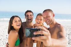 Amigos alegres que toman imágenes de ellos mismos Imagen de archivo libre de regalías