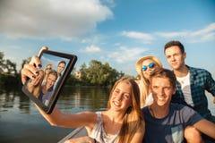 Amigos alegres que toman Selfie en un barco Fotografía de archivo