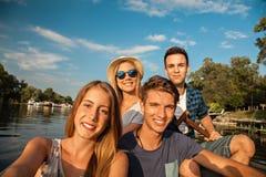 Amigos alegres que toman Selfie en un barco Imagen de archivo