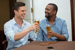Amigos alegres que tuestan los vidrios de cerveza en restaurante Imagen de archivo libre de regalías