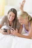 Amigos alegres que usan los teléfonos elegantes en cama Fotos de archivo